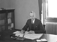 A balding white man in a three piece suit sits at a desk, pen in hand, with documents laid out before him.