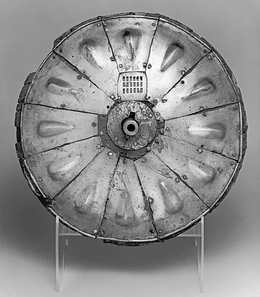 A round shield from the 16th century with a gun port in the center, allowing the user to fire a weapon from behind the shield