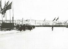 Une personne sur la glace, prête à prendre le départ. En fond, le public, des drapeaux et des montagnes.