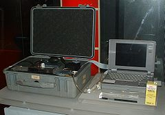 A machine that can facilitate euthanasia through heavy doses of drugs. It is possible in this image to see the laptop screen that leads the user through a series of steps and questions, to the final injection, which is done by motors controlled by the computer. This series of questions is supposedly to prevent unprepared users from undergoing Euthanasia.
