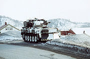 Vehicle in white winter camouflage. House roofs can just be seen behind and in the distance a range of snow covered mountains
