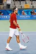 A dark-haired man is in a red shirt with white shorts and shoes and bandanna, which he is carrying his tennis racket in his right hand pointing towards the ground
