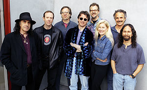 Seven men and one woman gathered together in front a photographic sheet, smiling at the photographer (Jay Blakesberg), wishing they were backstage at a concert about to start.