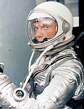 Glenn in a silver spacesuit, with his helmet on and clear visor down