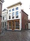 Woonhuis met monumentale lijstgevel en jongere winkelpui in een eclectische bouwstijl