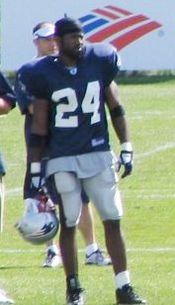 Color photograph of African-American football player Guss Scott in the dark blue, white and red uniform of the New England Patriots, standing on the sidelines at training camp.