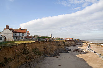 Happisburgh - The view of the cliffs from the end of Beach Road showing the precarious position of several houses, as the cliffs are being eaten away by coastal erosion.