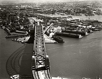 Walsh Bay - A 1937 image of the Sydney Harbour Bridge with Walsh Bay to the right of the Bridge in the centre of the image