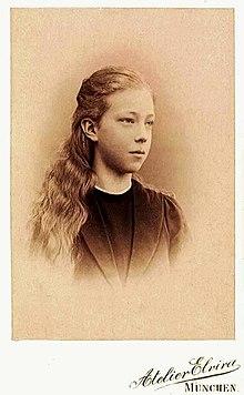 une jeune fille aux cheveux longs et aux yeux clairs, vêtue simplement regarde vers la gauche