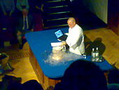 Sur un plan de travail bleu vif, le chef touille dans un récipient placé sur un braséro. La mixture dégage d'importants gaz. Près du cuisinier, un ordinateur allumé. Autour du plan de travail, des spectateurs sont assis en demi-cercle.