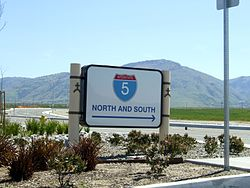 Highway directional sign in Wheeler Ridge, with Tehachapi Mountains beyond