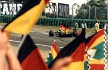 Photo d'une monoplace jaune et verte en piste. Son pilote agite un drapeau allemand.