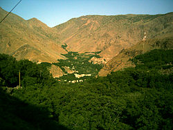 The village of Imlil in its wooded valley, surround by arid mountains. Taken early on a summer's morning, facing west. To the right a mobile phone mast sits incongruously on a nearby hill. Terracing of the valley is visible behind the village. Tall green trees are in the foreground.