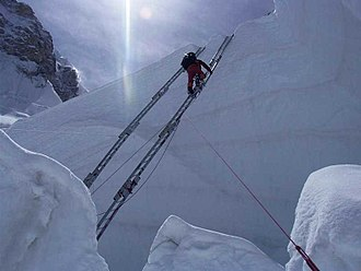 Khumbu Icefall - A mountaineer traversing a ladder in the Khumbu Icefall