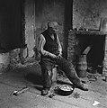 Interieur van een vervallen woning Een man schilt aardappelen, Bestanddeelnr 900-4658.jpg