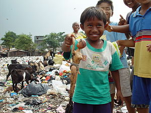 A boy from an East Cipinang trash dump slum shows his find, Jakarta Indonesia.