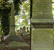 A granite obelisk, green from moss, in the shadow of a tree and surrounded by headstones