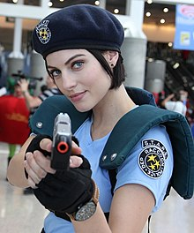 A woman wearing a costume at a convention from the waist up. She is wearing a dark blue beret, light blue shirt with shoulder armor and black gloves. She is pointing a pistol towards the viewer