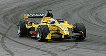 Une monoplace de F1 jaune, vue de trois-quarts, prend un virage à gauche.