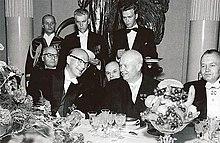 Foto av flere menn i formell bruk som sitter ved en bankett