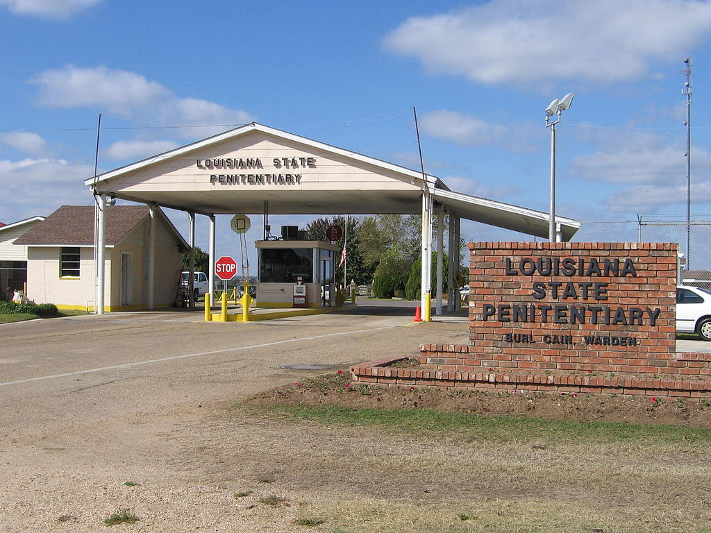 "The entrance to the Louisiana State Penitentiary has a guard house that controls entry into the compound—the sign says ""Louisiana State Penitentiary"" and ""Burl Cain, Warden"""