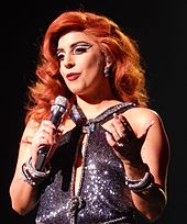 A woman with brown-red hair gestures with her left hand while holding a microphone in her right.
