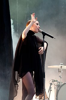 A dark blonde woman (Lykke Li) performs on stage at an outdoors festival.