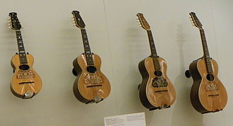 Mandolin orchestra - A manufacturer's idea which didn't take over, the mandolinetto or guitar-shaped mandolin by Howe-Orme. Pictured are a mandolin, tenor mandolin, octave mandolin, and cello mandola.