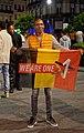 Man holding up We Are One Belgian flag during Euro 2020.jpeg