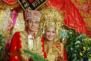 Bride - Bride and groom in traditional Minangkabau clothing of West Sumatra, Indonesia. Since the culture is matrilineal, i.e. gives special status for women, the bride is decorated with gold-coloured accessories to symbolize the wealth of their ancient kingdom.