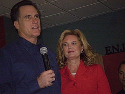 A tall, well-groomed pale-skinned man in his fifties with slightly greying dark hair wearing a dark blue shirt and holding a wireless microphone; to his side, a pale-skinned woman in her fifties with shoulder-length blond hair parted on the side, wearing red lipstick and a red jacket that almost obscures a double strand of white pearls around her neck; she is looking at him as he looks out at an unseen audience