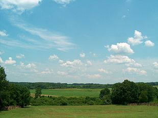 Photo shows a rural scene under partly cloudy blue skies. In the foreground a grassy hillside slopes down to a tree-filled ravine. On the other side are more open fields, with trees in the distance.