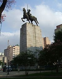 Photograph of a huge bronze statue atop a multi-story stone plinth depicting a mounted rider with upraised sword