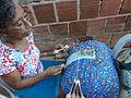 Mulher trabalhando na produção de renda de bilros.JPG