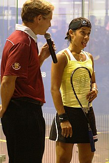 A man in a red shirt holds a microphone while a young woman in a yellow shirt holding a racket sticks her tongue out.