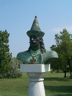 Obrázek tmavě zelenavé busty muže skalpakem na hlavě, knírem a vlasy po ramena. Na krku muž má řetěz a na něm zavěšený kříž.