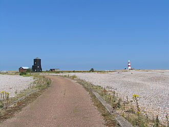 Orfordness Beacon - Looking north-east toward the Beacon, with its powerhouse to the right and barracks to the left. The Orford Ness lighthouse is on the far right. The lighthouse now operates a racon beacon.