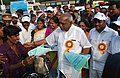 "P. Radhakrishnan handing over the Road Safety awareness pamphlets to a two wheeler driver after inaugurating the ""26th Road Safety Week"", at Marina Beach Road, in Chennai on January 16, 2015.jpg"