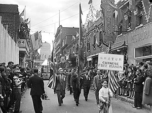 Chinatown, Montreal - A Victoria Day parade on De la Gauchetière Street in the 1945 Montreal Chinatown with the Bell Telephone Building in the background.