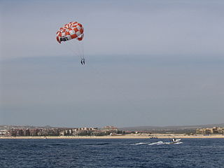 Parasailing aerial sport in which person is connected to a parachute and towed by a boat