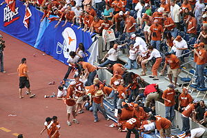 Guard rail - A guard rail collapses at a college football game, spilling fans onto the sidelines.