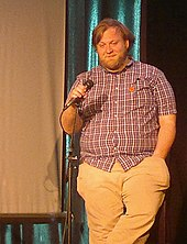 A brown-haired, bearded man in a red button-down shirt and white pants holds a microphone while his other hand rests in his trouser pocket.