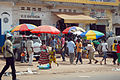 People in Guinea Bissau visit shops along a busy street.jpg