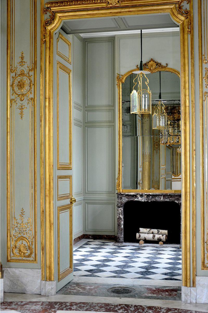 Vue de l'antichambre depuis le salon central montrant le miroir du fond et le dallage de marbre.