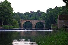 A stone two-arched bridge across a river, viewed along the river, both ends hidden by trees. A weir is in front of the bridge, at the right end of which is a two-storey building.