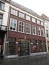 foto van Huis met witgeverfde lijstgevel, lage bovenverdieping en houten kroonlijst met verkroppingen en ruitmotieven