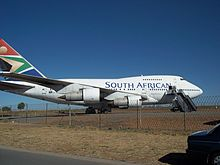 "A Boeing 747SP, a shortened Boeing 747-100, is parked at an fenced-off airport, facing right. The aircraft's engines feature prominently, as a mobile stairway is placed next to one of its doors under the ""N"" in South African."