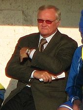 The upper body of a grey haired man sitting in the dugout with crossed arms. He has black trousers, a grey jacket, white shirt and a gold tie. He is wearing glasses with red tinted lenses a has a watch on his left wrist. In his right hand is a rolled up piece of paper.