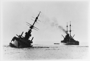 A battleship leaning heavily to the right, about to capsize