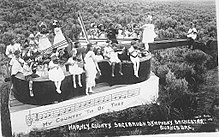 Black and white image of a group of children holding stringed instruments, sitting and standing in various position on a violin-shaped float in an open field.